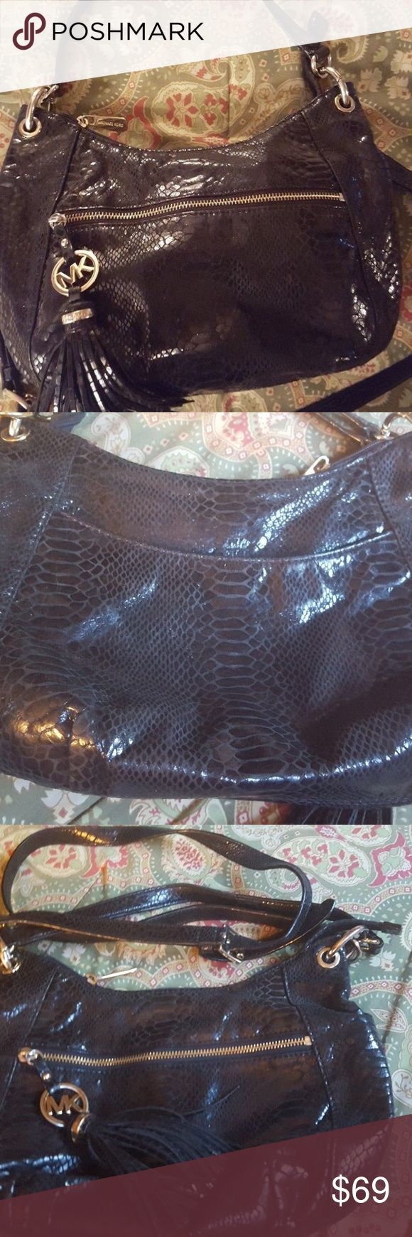 """Michael Kors black handbag shoulder bag purse No stains or defects.  Used as handbag or a shoulder bag.  Shoulder bag straps are 20"""" but can be adjusted and handbag straps are 9""""   Front of bag has zip compartment.  Bag has MK charm and frills below it with gold circular charm above it also reading """"Michael Kors.""""  Bag zips on top (again, zipper has """"Michael Kors"""") and opens to 1 compartment.  Back of bag has zip pocket. Length 13"""", height 9.5"""".  Located in a smoke-free home. Michael Kors…"""