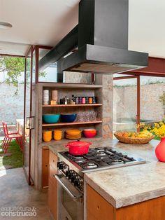 Ilha e armários de alvenaria moldada na obra desenham a cozinha. A coifa fica presa no teto e seu duto de exaustão atravessa o vidro até o exterior. Projeto do escritório Apiacás Arquitetos.