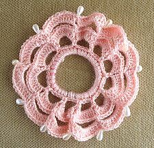 Free pattern - how to crochet a scalloped edge hair scrunchie.  This pretty hair accessory is decorated with pearl bead