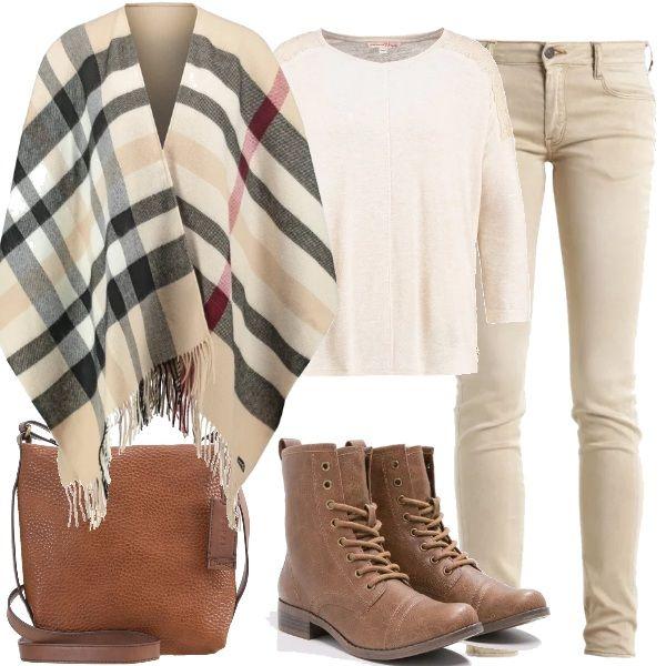Propongo maglione con scollo tondo, jeans con tasche posteriori e laterali, mantella a scacchi, stivaletti con lacci e punta tonda e per finire borsa a tracolla.