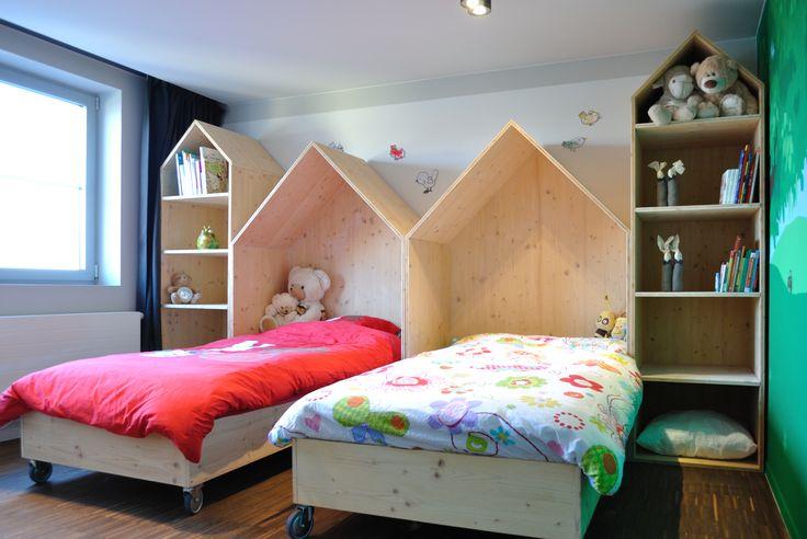M-INT interieurarchitectuur  Kasten voor de kinderkamer in de vorm van huisjes. Bedden op wielen: als de kleine kindjes naar de lagere school gaan en een bureau nodig hebben, kunnen de bedden wegrollen en de grote huisjes veranderen met een extra legplank in een bureau.