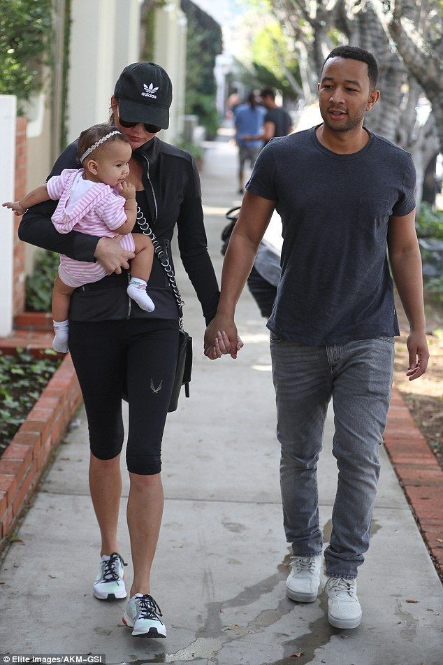 And baby makes three: John Legend held hands with Chrissy Teigen as she toted their baby g...