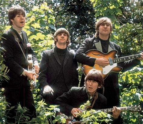 """This undated handout photo shows members of The Beatles walking and singing as they are filmed during a promotional video for their song """"Rain."""""""