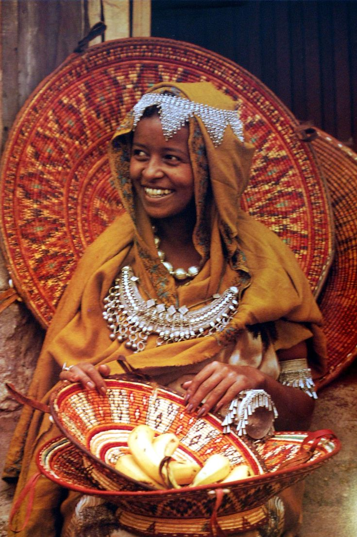 Africa   Woman from Harer, Ethiopia, wearing traditional jewellery and surrounded by locally made baskets   Image taken from Angela Fisher's Africa Adorned publication