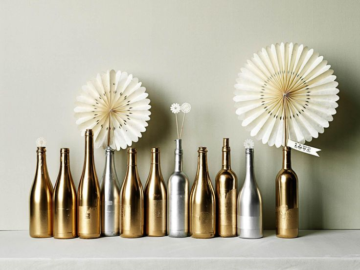 diy | spray paint wine bottles with metallic paint for centerpieces and top with whimsical paper fans | via: BHLDN