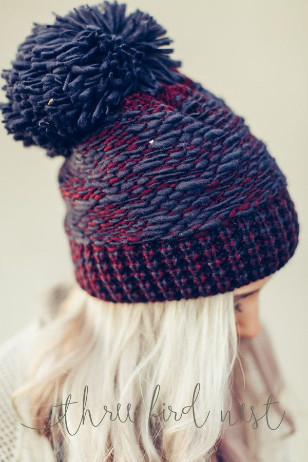 Our amazing silhouette in a chunky knitted oversized pom-pom beanie is a beautiful navy blue and red multi color yarn. Oversized pom pom topper.