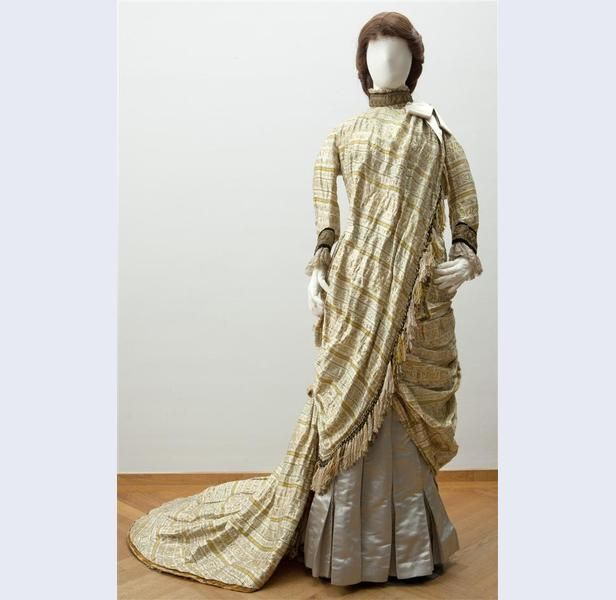 Reception or evening gown, Worth, ca. 1879. Silk brocade with woven oriental motifs, trimmed with silver and gold thread on silk satin and cotton machine lace.