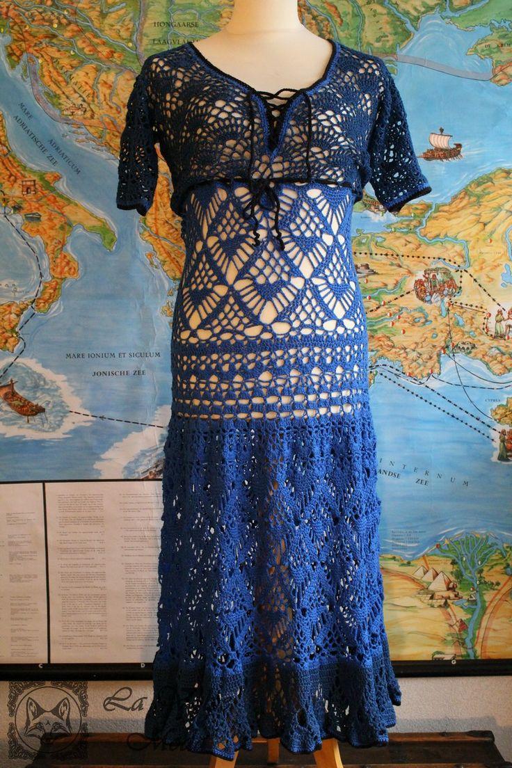 Gehaakte lange denim blauw met kobalt jurk, afgewerkt met zwarte rand. De jurk is met diverse patronen gehaakt, heeft een uitlopende rok en is aansluitend op de heupen. Diepe V-hals met vetersluiting, aanrijgkoordje onder de buste en 3/4 mouwen. Kleuren:…Lees meer ›