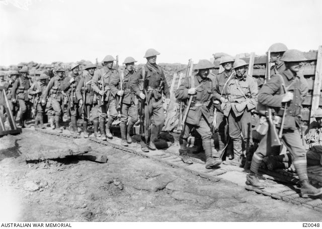 Unidentified Australian soldiers walking along a duckboard track on their way to the front line trenches in Northern France. Breastworks reinforced with timber and sandbags can be seen behind the line of men. The first Australian battalions moved into the front line on the Western Front on 7 April 1916. [EZ0048   Australian War Memorial]