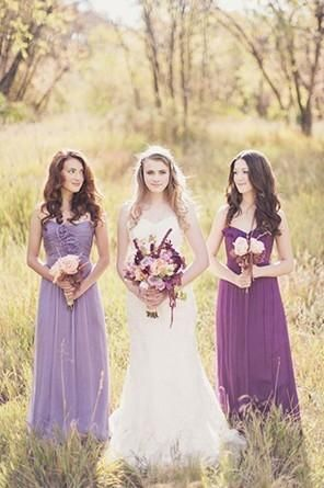 Bridesmaids in different colored purple dresses in an open field holding lavender bouquets @myweddingdotcom