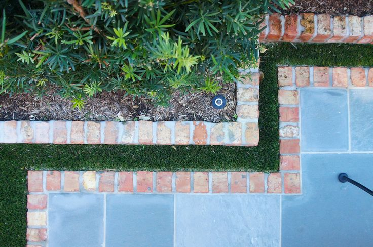 Red brick borders gray slate patio separated by garden with synthetic lawn.