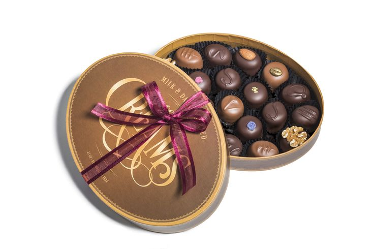 An assortment of traditional cream centres enrobed in premium milk and dark chocolate in a large brown oval ribboned presentation box.