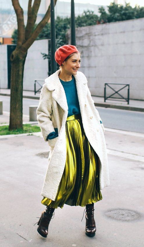 Jenny Walton in a metallic skirt, cream jacket, black booties, and red beret