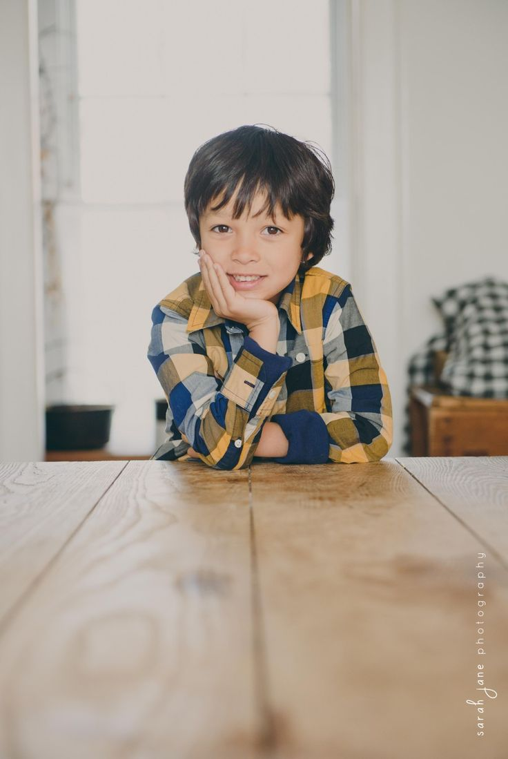 Boy leaning on a table in a farm house