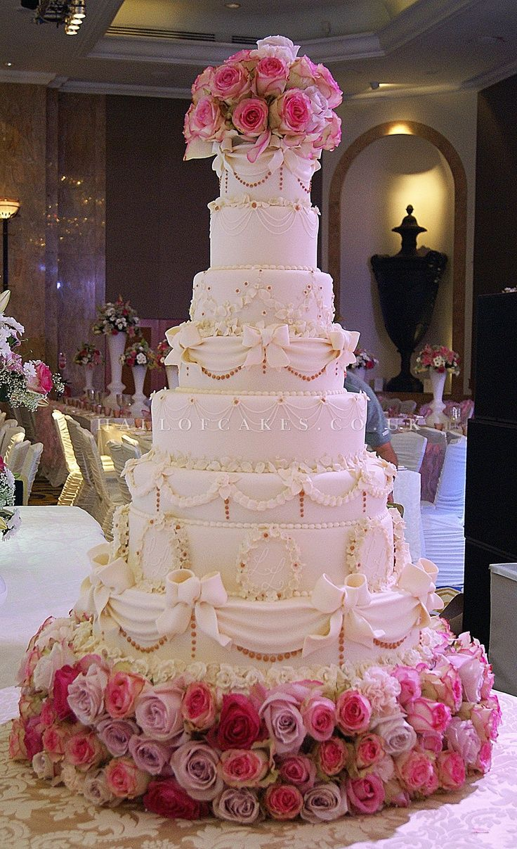 A very tall, classic wedding cake gets taken to the stratosphere with the addition of an exquisite floral base and matching topper.
