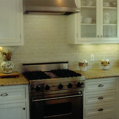 Subway tile tumbled marble with Venetian Gold granite tops on white cabinets