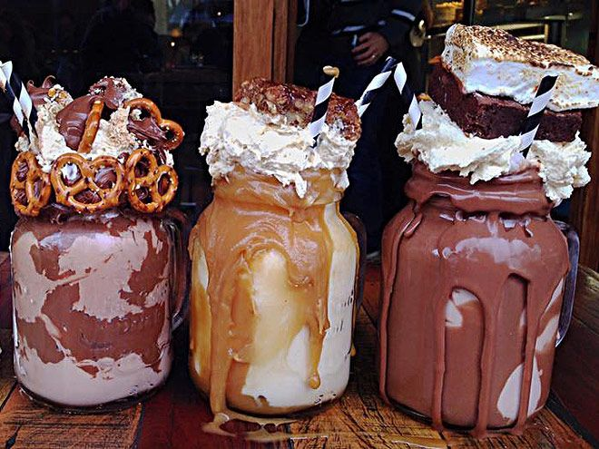 The creamy concoctions, which overflow from mason jars, are topped high with whipped cream and sugary sweets like pretzels, whole brownies, chocolate syrup and more.