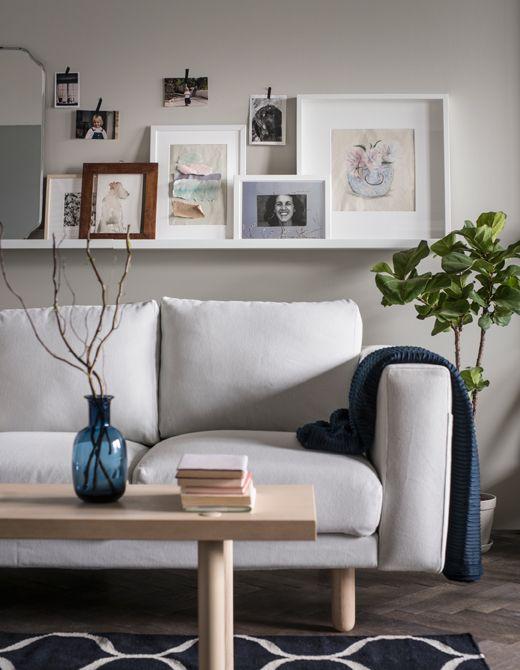 In un soggiorno, cornici e quadretti sono disposti su una mensola per quadri; sulla parete, invece, sono fissate foto più piccole con del nastro adesivo decorativo - IKEA