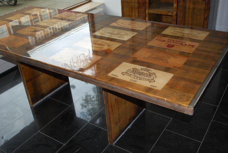 Wijntafel donker grenen van gerecycled hout (steenschotten). Tafelblad met geïntegreerde wijnkistjes afgewerkt met epoxy coating. Formaat 95x220 cm.