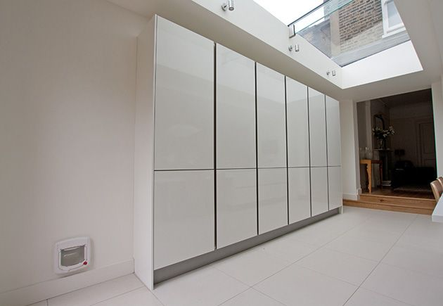 Streamlined handleless tall cupboard units designed to fit seamlessly within the new ktichen extension and a gloss white finish beneath the glazed ceiling reflect light for a brighter room effect.