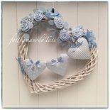 Grande cuore di vimini bianco decorato con 5 roselline di piquet di cotone azzurro ,rametti di feltro e fiocchi in canetè sempre azzurri.  Al centro tre cuori imbottiti in piquet di cotone di tre f...