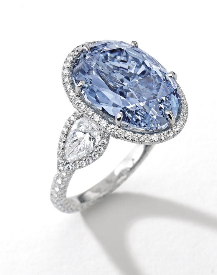SUPERB AND RARE FANCY VIVID BLUE DIAMOND AND DIAMOND RING. Set with an oval brilliant-cut diamond weighing 10.10 carats, flanked by two pear-shaped diamonds, to the circular-cut diamond surround, gallery and hoop, mounted in 18 karat white gold. Ring size: 6¾. Estimate 30,300,900 - 36,103,200 USD // LOT SOLD 32,013,223 USD. GIA / Fancy Vivid Blue Colour, Internally Flawless, inscribed with 'De Beers Millennium Jewel 4' [S. MAGNIFICENT JEWELS & JADEITE - 05 APRIL 2016 - HONG KONG]