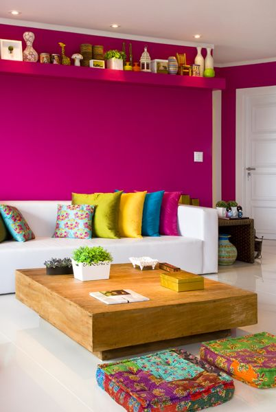 Arquiteta e decoradora Andrea Murao. Bright pink walls with high level shelves, white floorboards and sofa with colourful cushions and floormats.