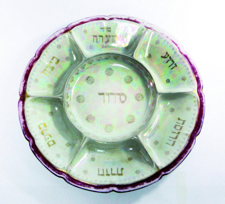 Large porcelain plate for the Seder night. C arlsbad, Bohemia (Czechoslovakia), beginning of the 20th century. 35 cm. diameter, rim raised 4 cm. Maker's mark on the bottom, with the imprint '325'.  6 indentations for the simanim of the seder, with a round indentation for maror. Gilt text and decorations. Nice margins in maroon and gold.  Rim faded in the margins and slightly rubbed. Overall very fine condition.