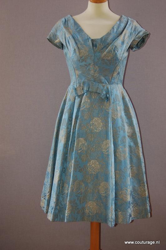 Cocktailjurk van helderblauwe zijde(?) met groot motief van rozen met bladeren in goudbrokaat (1950E022)