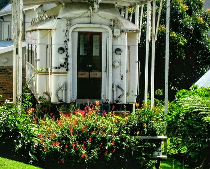 A train carriage from the period is part of the landscaping at a village home. It's an active, living village.