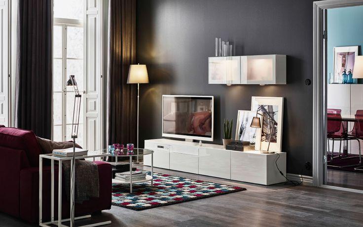 Sala com um móvel de TV em branco brilhante e um sofá de dois lugares com chaise longue em roxo avermelhado Combinado com uma mesa de centro redonda com tampo em vidro