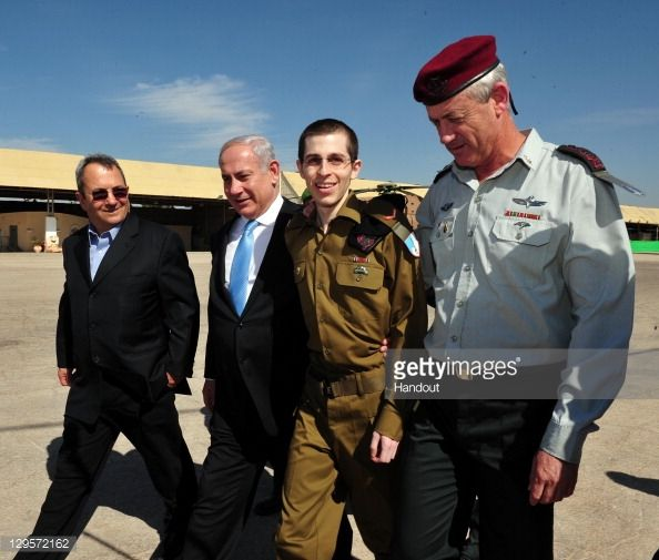 In this handout photo provided by the Israeli Defence Force, freed Israeli soldier Gilad Shalit (2nd R) walks with Defence Minister Ehud Barak (L), Israeli Prime Minister Benjamin Netanyahu (2nd, L) and IDF Chief of General Staff Benny Gantz (R) at Tel Nof Airbase on October 18, 2011 in central Israel. Shalit was freed after being held captive for five years in Gaza by Hamas militants, in a deal which saw Israel releasing more than 1,000 Palestinian prisoners.