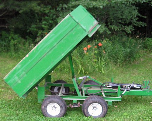 """This is a combination wood splitter and dump trailer I designed and built to reduce handling while hauling firewood out of my woodlot. Roughly 5'x7', the trailer has angled front corners to slide past overhanging trees. The splitter and dump use the same 4"""""""" cylinder and valve, powered by tractor hydraulics. Wood is split on the tongue, tossed in the back, then dumped at the woodshed. The trailer is regularly used for dirt, rocks and manure as well. The splitter easily splits anything I want…"""