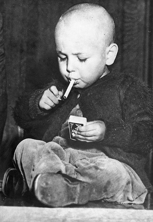 22 months old boy lights a cigarette. Los Angeles. Photo ca.1920/30.