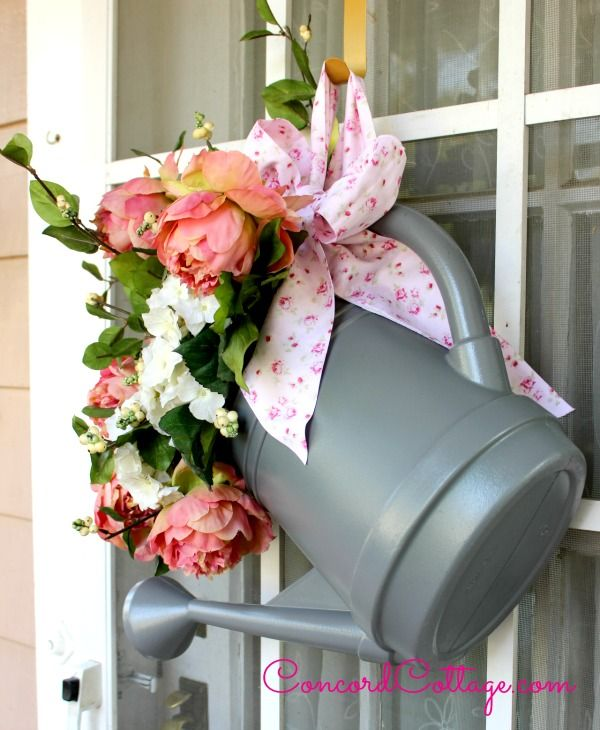 Watering Can Door Hanger you can make by spray painting an old watering can and adding flowers