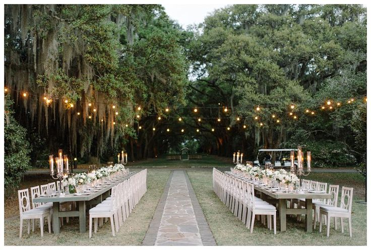 Outdoor wedding reception at the Legare Waring House in Charleston, SC featuring long rows of tables beneath garden lights, set with tall candelabras and centerpieces of white florals. Event design by Ooh! Events, florals by Out of the Garden, image by Sean Money + Elizabeth Fay.