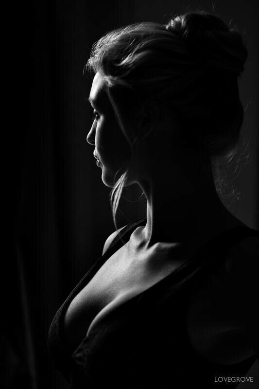 Low Key Light technique used to create a black and white creative portrait of a busty woman.