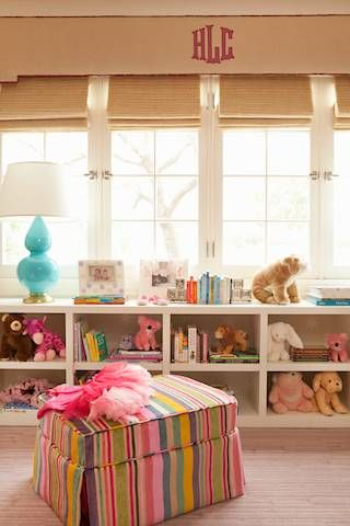 Girls room with custom storage for toys and books. Delicious striped ottoman and aqua lamps. Monogrammed window pelmet with roman shades. Absolutely precious! #jennfdesigns #jennfeldmandesigns