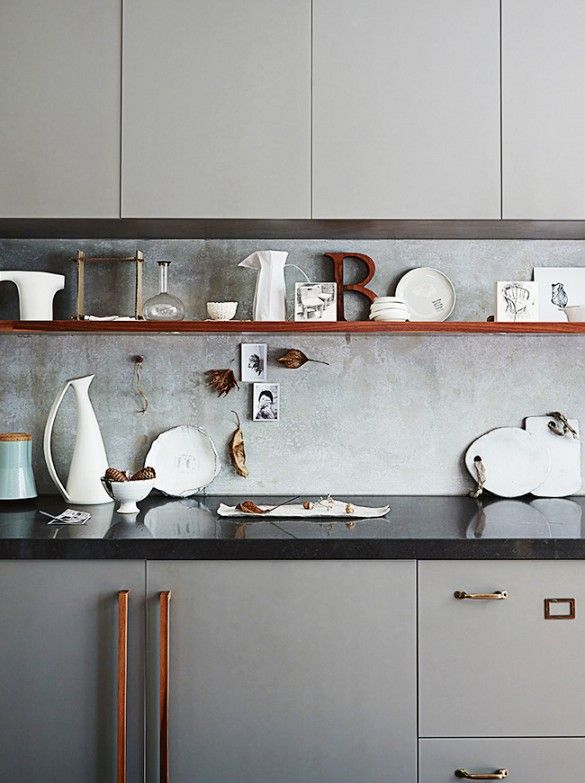 Modern kitchen with gray cabinets, tonal trinkets and objects on display.