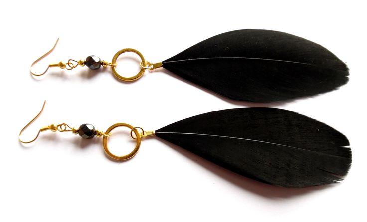 Örhängen i guldplätering med kristaller och svarta fjädrar.  Längd: 13cm