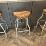 Contemporary looks with a touch of midcentury modern appeal, this distinctive swivel bar stool anchors any space with a dash of industrial style. Constructed from steel in a glossy finish, this handsome design features four curvy legs, strap side bracings, and black foot pads. As solid ash wood seat lends the piece warmth and character, while a threaded iron shaft adjusts the seat height to suit a variety of tables and counters with the crank of a side handle. Try pulling a few up to your…