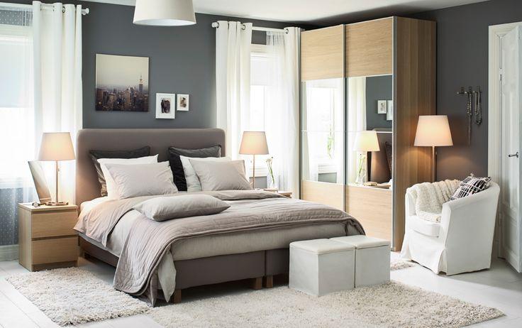 Ein mittelgroßes Schlafzimmer u. a. mit LAUVIK Boxbett in Dunkelgrau mit festen HAMARVIK Matratzen, kleinen Kommoden als Nachttischen und einem großen Kleiderschrank mit weiß lasierten Schiebetüren in Eichenfurnier und Spiegelglas