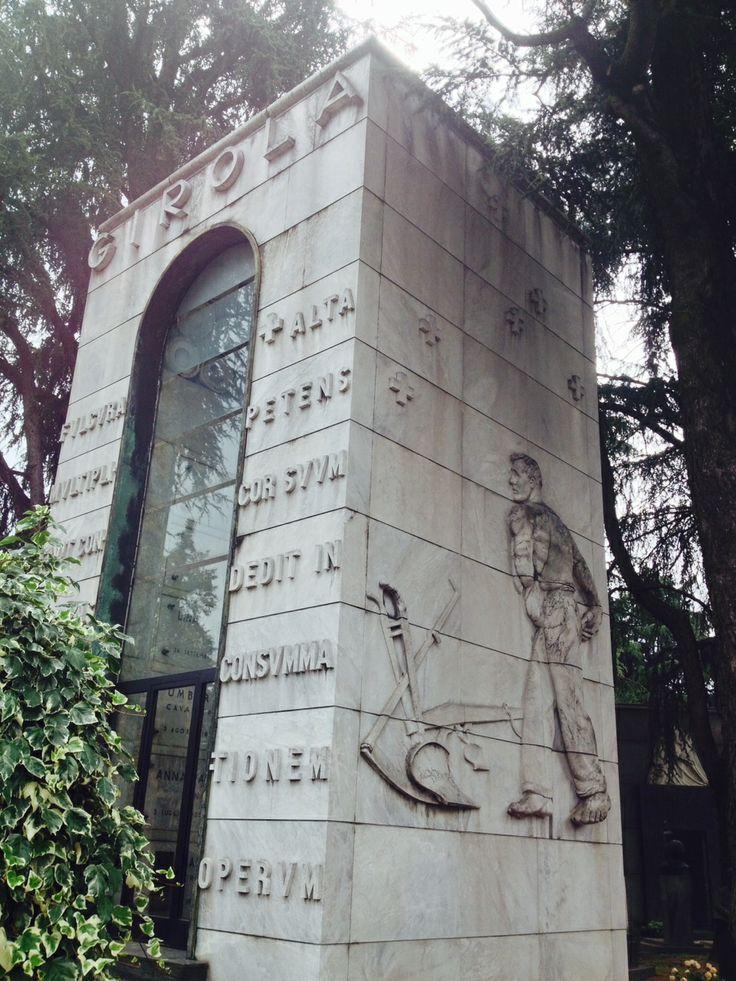 La famiglia Girola fondò nel 1906 un'impresa edilizia e si impegnò nella costruzione di impianti idroelettrici. Nell'edicola progettata da Portaluppi prendono vita le figure di un minatore e di un contadino scolpite da Giannino Castiglioni