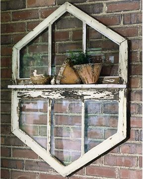 Here, two salvaged windows are joined together and fit with a board to create a shelf