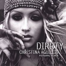 "Picture with the words ""DIRRTY CHRISTINA AGUILERA FEATURING REDMAN"" under the image of Christina Aguilera's face. She has a nose earring, a tight fitting cap, and mascara-darkened eyes. Her hands are partially blocking the view of her face."