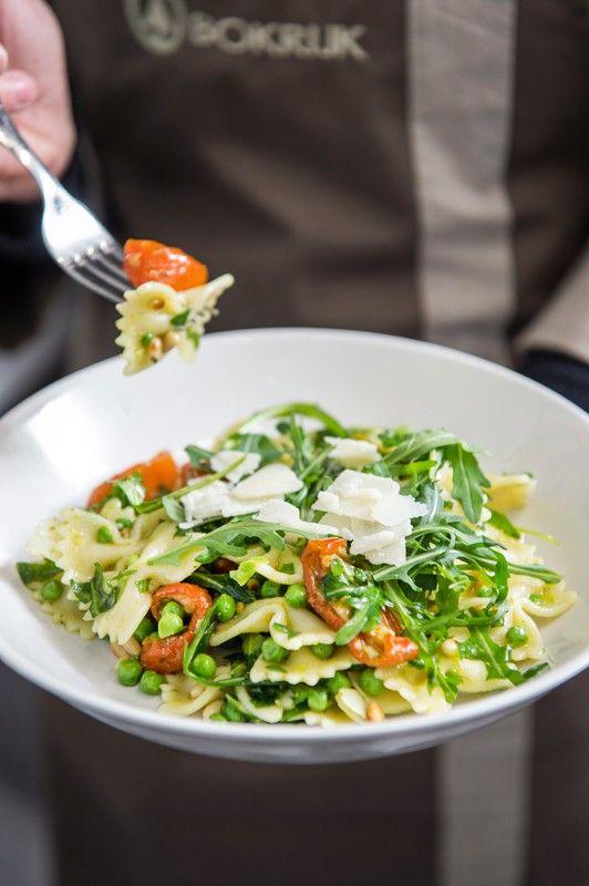 1. Rooster de pijnboompitten in een warme pan. Laat afkoelen. 2. Kook de pasta, voeg na 10 min de erwtjes toe en laat nog 5 min verder koken. Giet af en laat uitlekken. 3. Knip de rucola iets fijner. 4. Meng in een grote kom de pasta met de zongedroogde tomaatjes, pijnboompitten en rucola. 5.