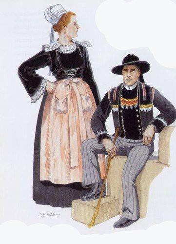 Costumes de Scaer-Le Faouet -La femme est coiffée du kiz-fouen et a une colerette de lingerie brodée - la jupe est de mérinos, le corselet et le gilet de velours mousseline. Le tablier est de damas. L'homme a un chapeau de feutre à ruban demi-large de velours ; veste de drap ornée de velours et de broderies de soie et pailletée d'argent. Pantalon de drap