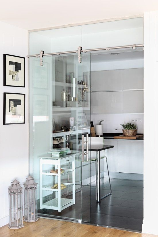 A glass door on a barn door track opens up a what would have been a dark, cramped kitchen.