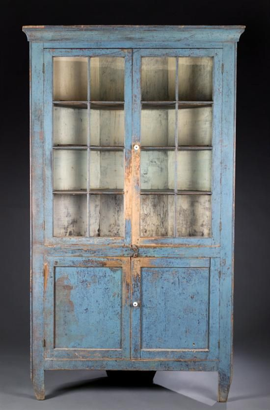 """PAINTED GLAZED-DOOR CORNER CUPBOARD.   Probably southern Indiana, mid 19th century, poplar. One-piece with two twelve-pane upper doors and two paneled lower doors, and resting on cutout feet. Retains an old blue paint over earlier yellow. Minor imperfections. 85 1/2""""h. 49 1/2""""w. 17 1/2""""d., requires a 36"""" corner."""