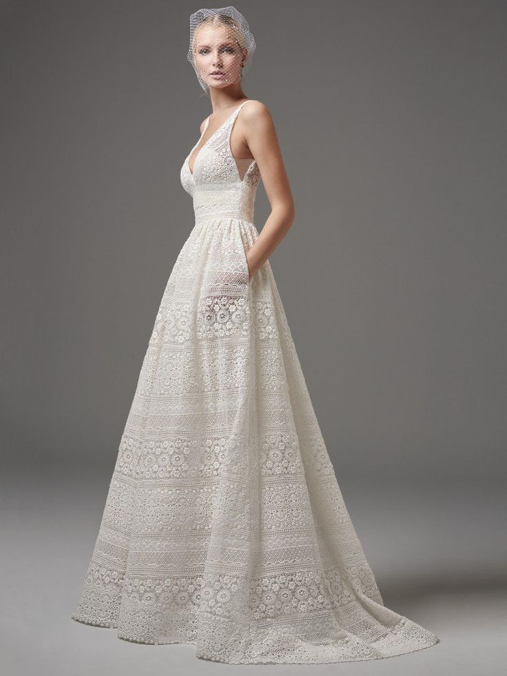 This chic, boho-inspired A-line features sheer pockets and patterns of eyelet lace, floral motifs, and scalloping. Sheer lace straps complete the V-neckline and sexy square-back. Finished with zipper closure. Detachable tulle overskirt with lace waistband sold separately.